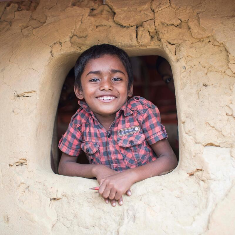 Photo of a Rohingya refugee boy looking out of a mud building window and smiling.
