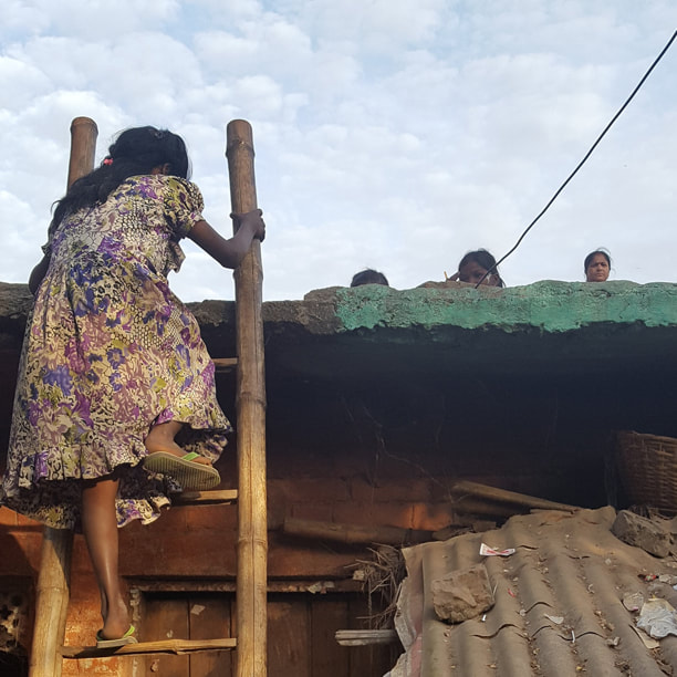 Photo of an Indian girl, climbing a ladder to reach a rooftop school in Patna.